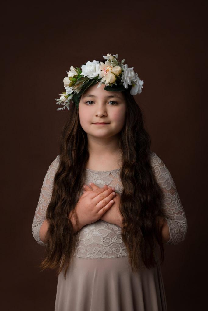 Jeune fille portant une robe couleur café et une couronne de fleurs
